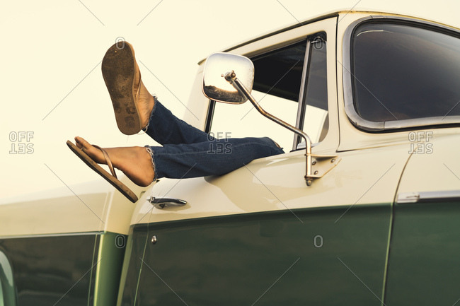 Legs of young woman out of pickup truck window at Newport Beach, California, USA