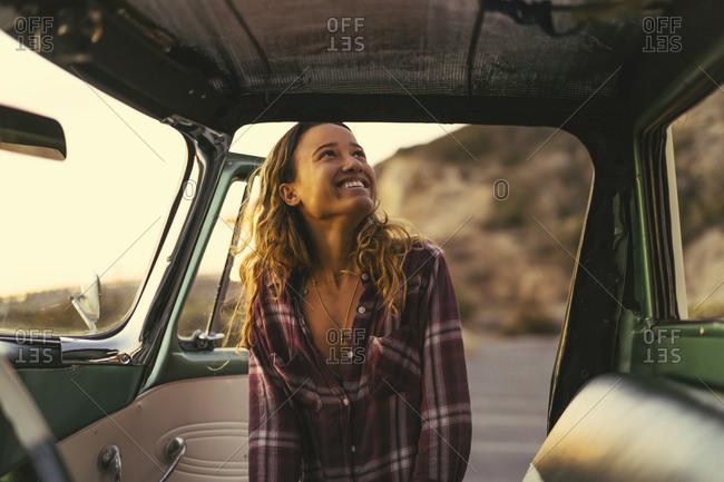 Happy young woman at pickup truck door at Newport Beach, California, USA