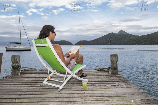 Woman sitting on a deck chair on a pier, Ilha Grande, Rio de Janeiro, Brazil