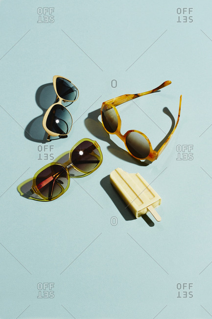 Sunglasses and yellow ice lolly on light blue background