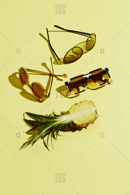 Sunglasses and pineapple on yellow background