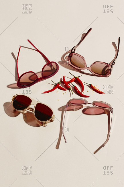 Sunglasses and chili peppers on pink background