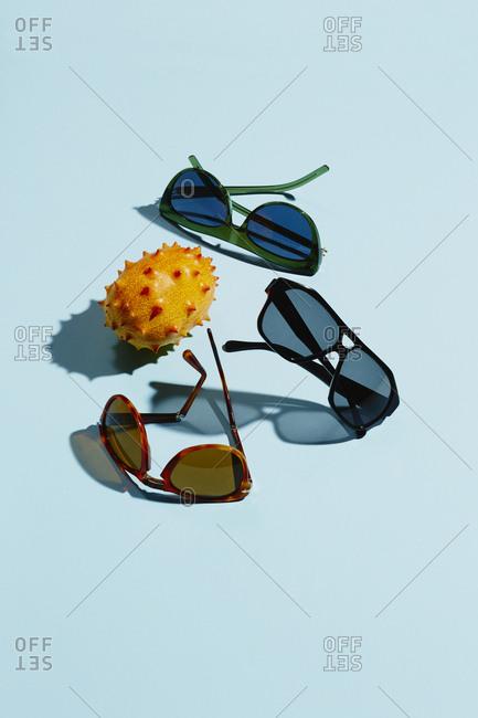 Sunglasses and orange kiwano fruit on light blue background