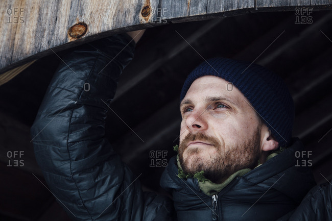 Portrait of a man with a beard wearing a winter jacket and knit hat