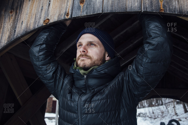 Portrait of a man with a beard wearing a winter coat and knit hat