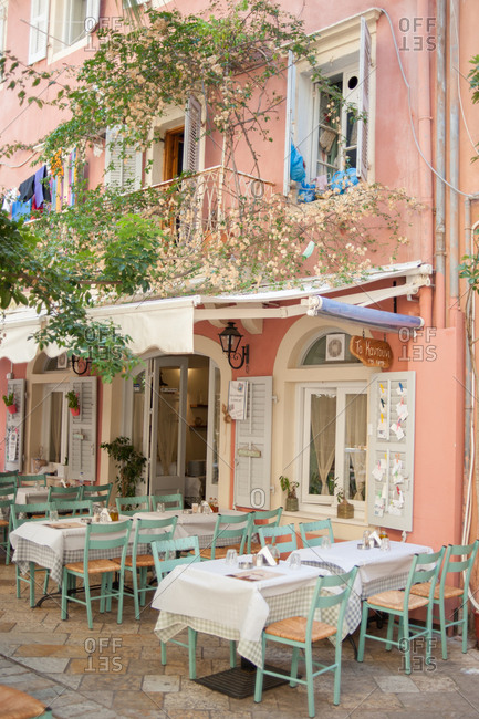 September 25, 2016 - Corfu, Greece: Sidewalk cafe tables in front of pink building