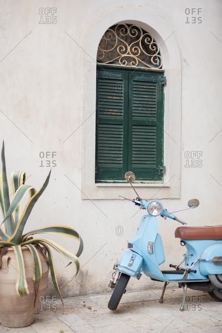 September 25, 2016 - Corfu, Greece: Blue motor scooter parked, near window