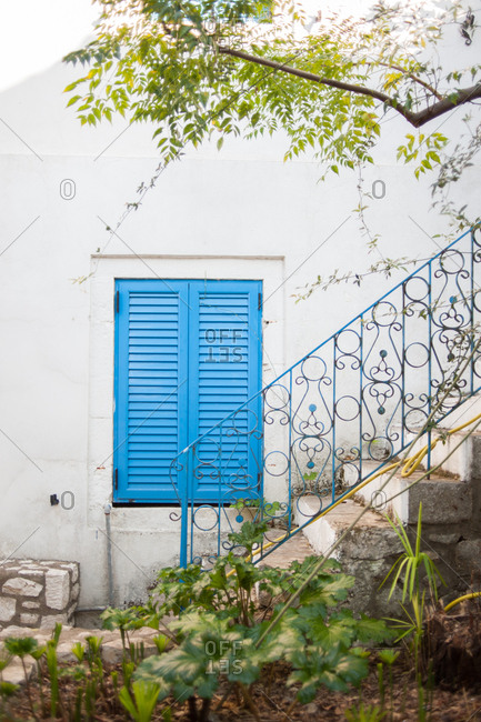 Blue shuttered window on white stucco wall of house in Greece