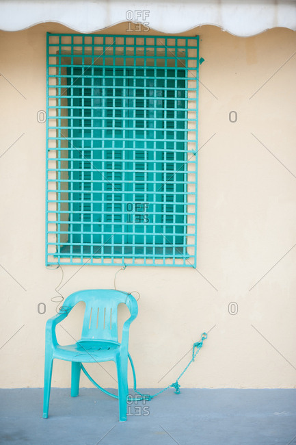 Turquoise painted window grate and chair in village of Vathy, Ithaca, Greece