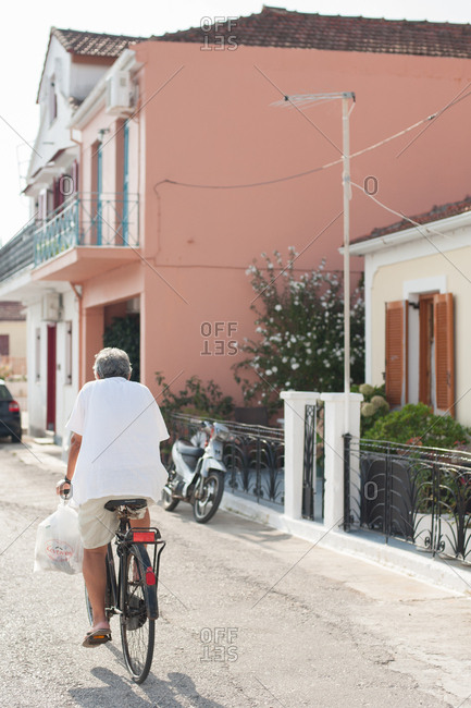 October 3, 2016 - Ithaca, Greece: Man riding bicycle on Vathy street