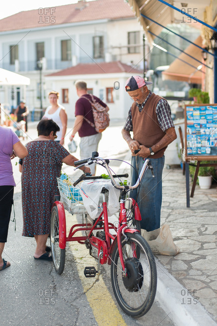 October 3, 2016 - Ithaca, Greece: Woman buying goods from man on bicycle in Vathy