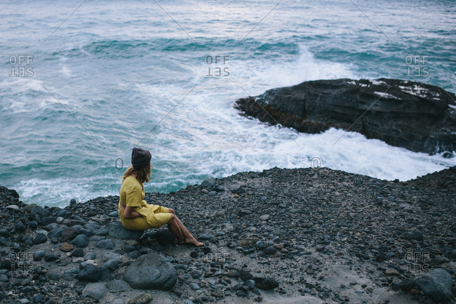 Woman wearing a dress sitting on a rock overlooking the ocean