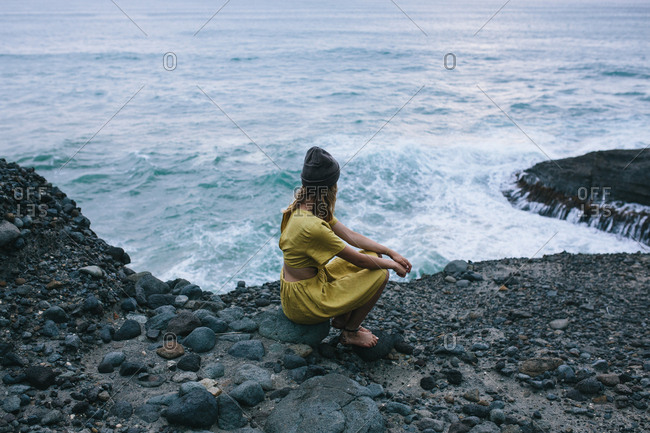 Woman sitting on a rock and looking out over the ocean as the waves are rolling in