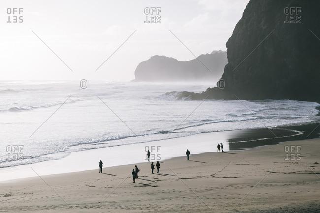 People walking on a sandy beach below tall rocky headlands