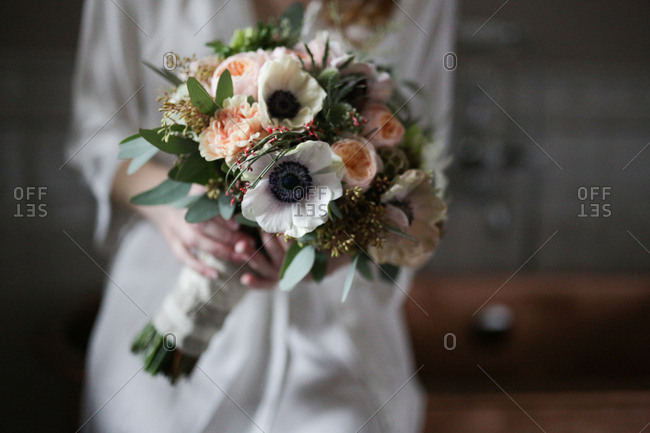 Bride in a satin robe holding a bouquet of white and pink flowers