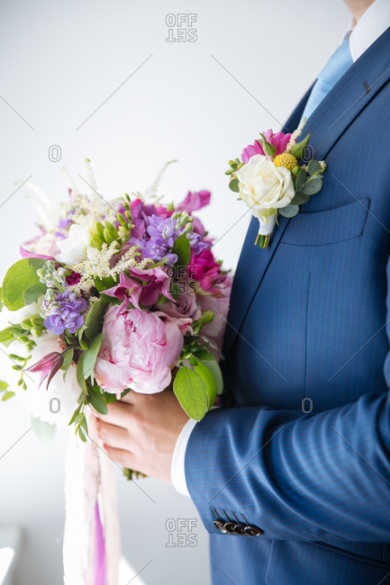 Groom holding a bouquet of purple and pink flowers