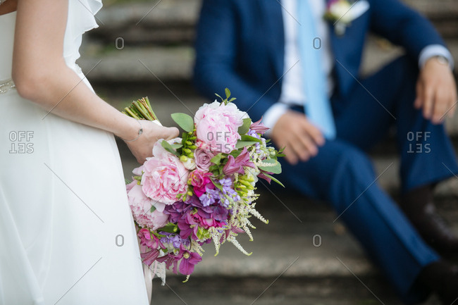 Bride standing in front of her groom holding a bouquet of pink and purple flowers