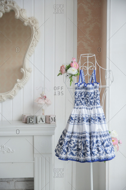 Blue and white sundress hanging from a wire mannequin in an elegant room