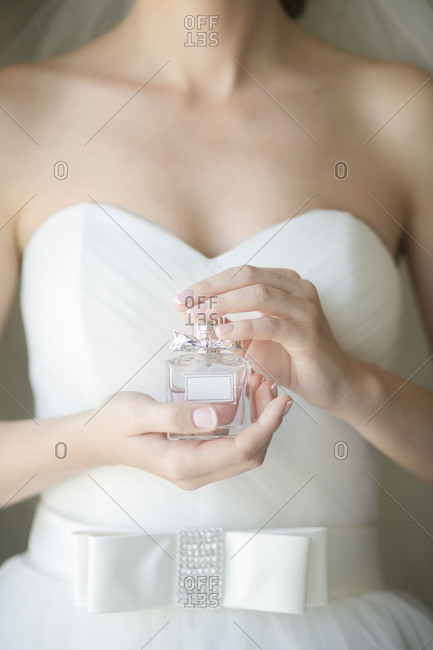 Bride in a white gown holding a bottle of perfume