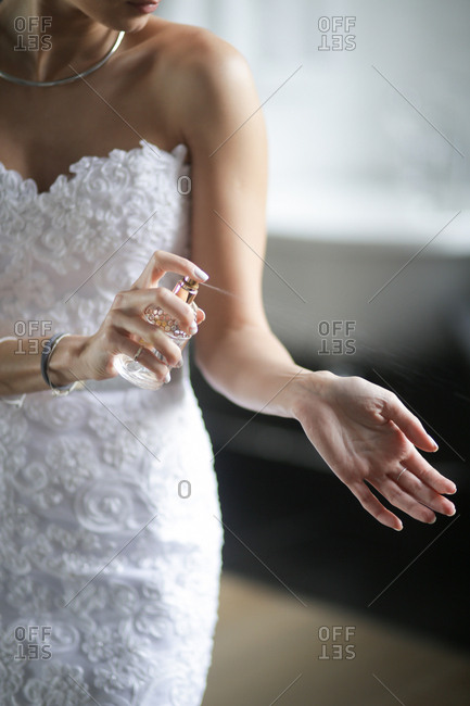 Bride in a white gown spraying perfume on her wrist