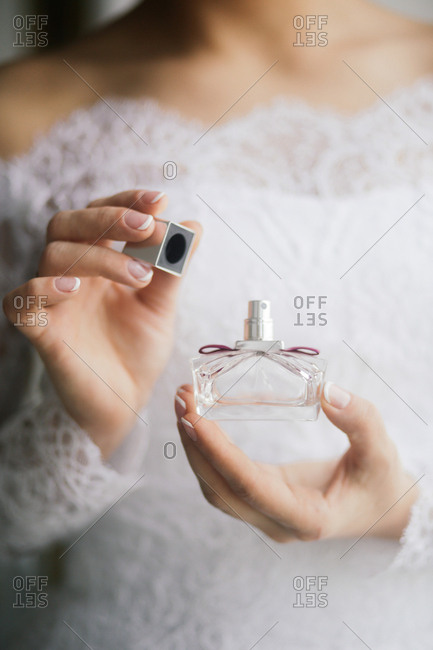 Bride in a white gown holding the lid and bottle of perfume
