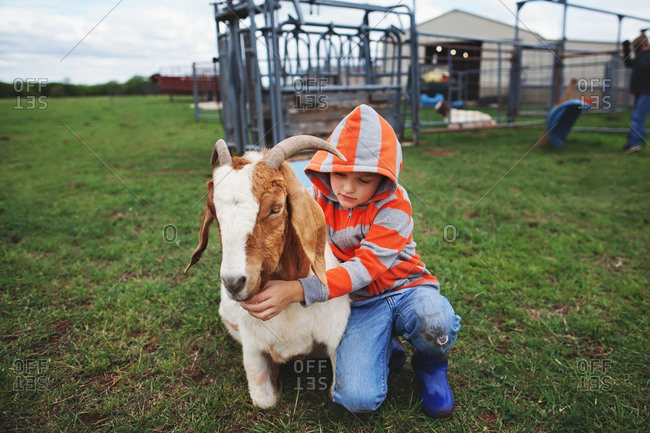 Boy kneeling next to a goat and hugging it