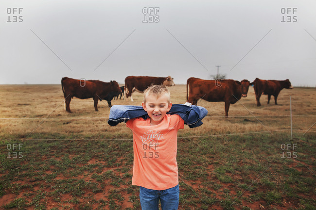 Boy standing and smiling in front of a field of cows