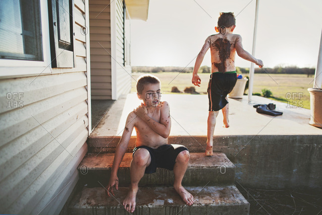 Two brothers playing in mud beside the porch of a country house