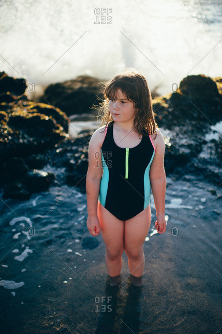 Girl in a swimsuit standing in a tidal pool on a beach