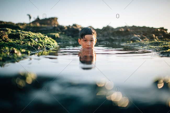 Head of a little boy wading in a tidal pool among mossy rocks