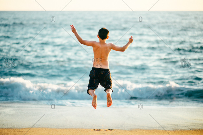 Boy on a beach leaping into the air