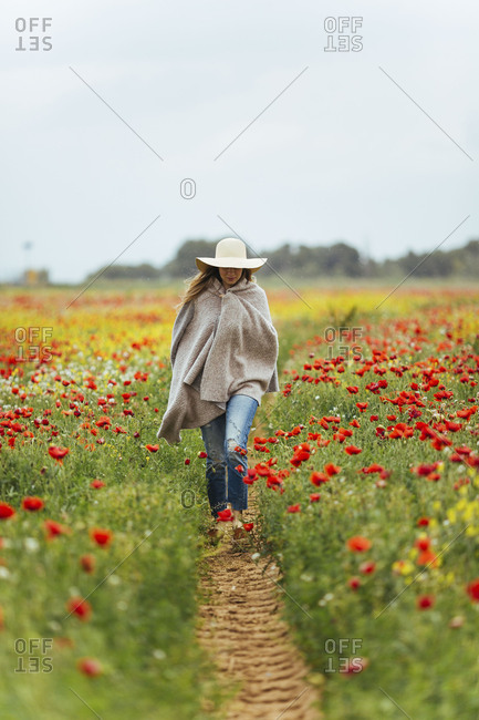 Woman wrapped in a blanket walking through a field of flowers