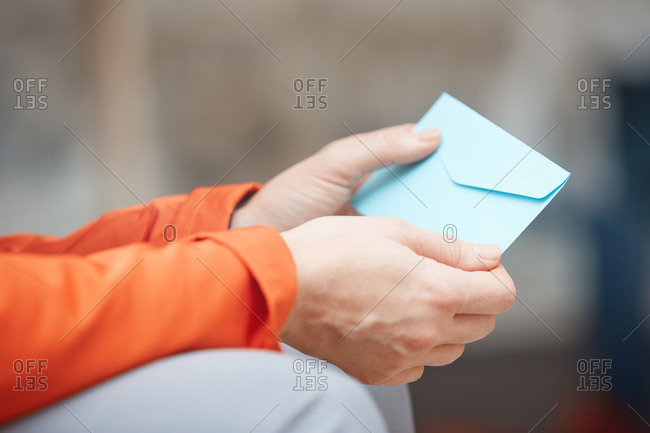 Sitting woman holds envelop with letter