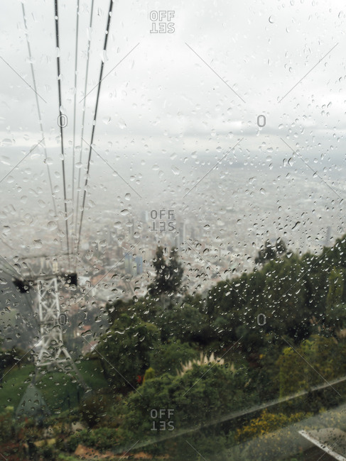 View of Bogota city through raindrops in Montserrat cable car window, Bogota, Colombia