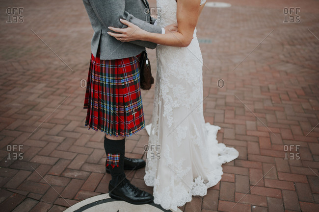 Groom in a plaid kilt embracing his wife on a brick pathway