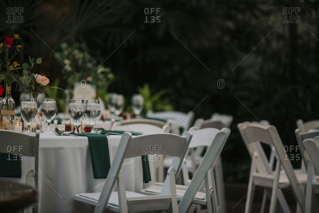 White tables and chairs at a wedding reception in a conservatory