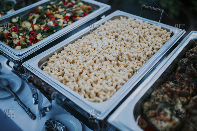 Serving trays filled with pasta and vegetables at a buffet-style reception