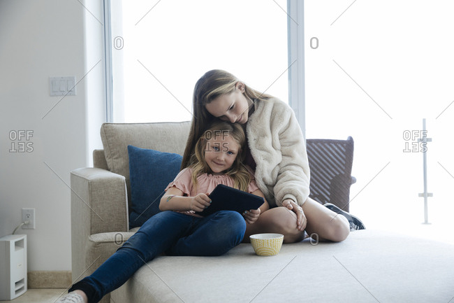 Portrait of cute girl holding digital tablet while sitting on chair with big sister