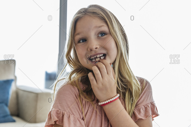 Close-up of cute girl looking away while showing missing tooth