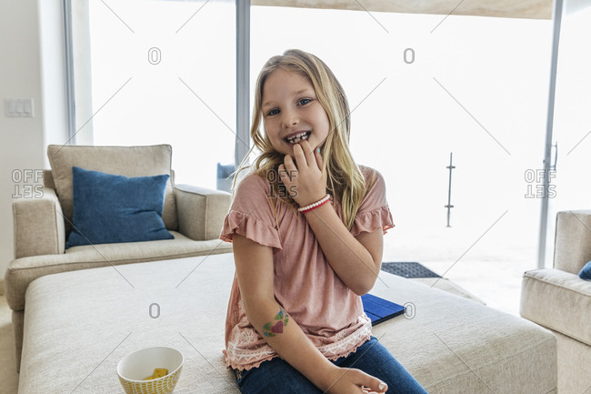 Portrait of cute girl showing missing tooth while sitting on ottoman at home