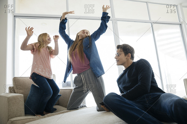 Young man looking at playful sisters dancing in brightly lit living room