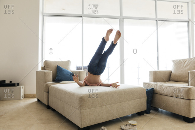 Young girl lying with feet up on ottoman in living room