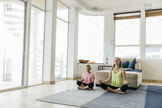 Full length of sisters practicing yoga in lotus position at home