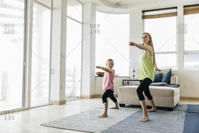 Sisters practicing yoga in living room