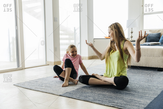 Happy teenage girl gesturing practicing yoga with sister at home