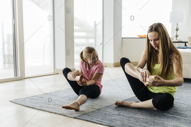 Teenage girl teaching sister to sit in lotus position on rug at home