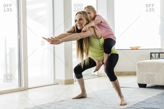 Happy teenage girl carrying sister while doing yoga in squat position at home