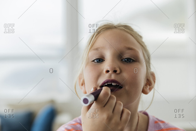 Portrait of young girl applying lipstick at home