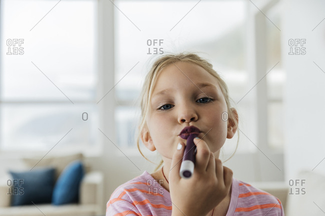Portrait of confident girl puckering lips while applying lipstick
