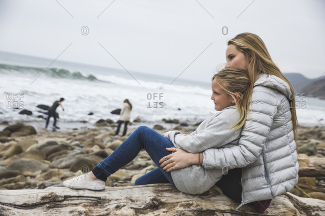 Portrait of sisters sitting on rocky beach